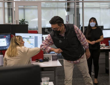 Employees elbow bump at a JLL office in Menlo Park, Calif., last September. With the delta variant surging, mask mandates are returning and some employers are now requiring employees to be vaccinated before coming to the office. (David Paul Morris/Bloomberg via Getty Images)