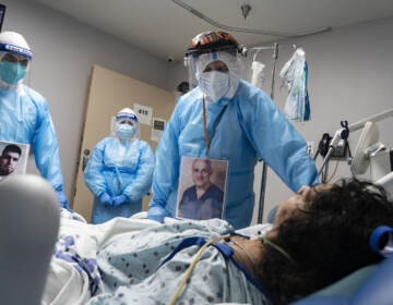 Medical staff members check on a patient in the COVID-19 Intensive Care Unit