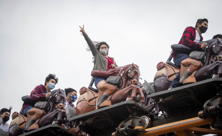 Park patrons ride the Pony Express roller coaster ride, one pictured in center wearing a mask and throwing up a peace sign