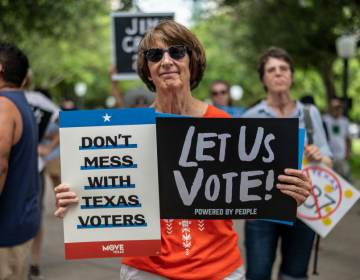 A woman holds signs at a rally at the state Capitol on June 20 in Austin, Texas, to fight SB7, a controversial voting bill. (Sergio Flores/Getty Images)