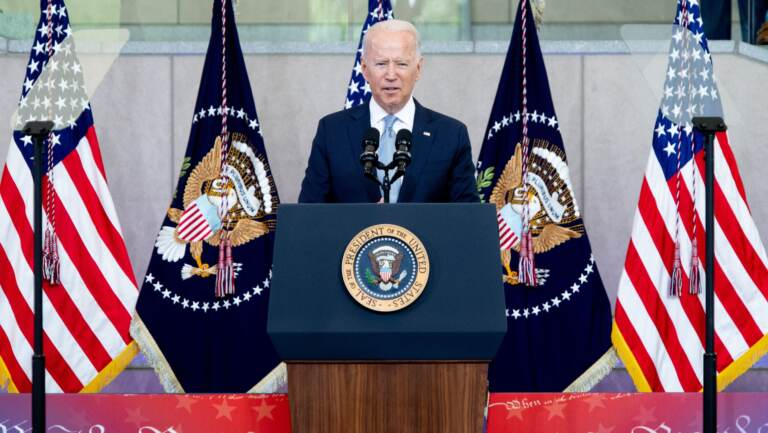 Biden speaks from a podium with American flags behind him at the National Constitution Center