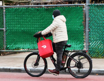 A DoorDash delivery person rides their bike