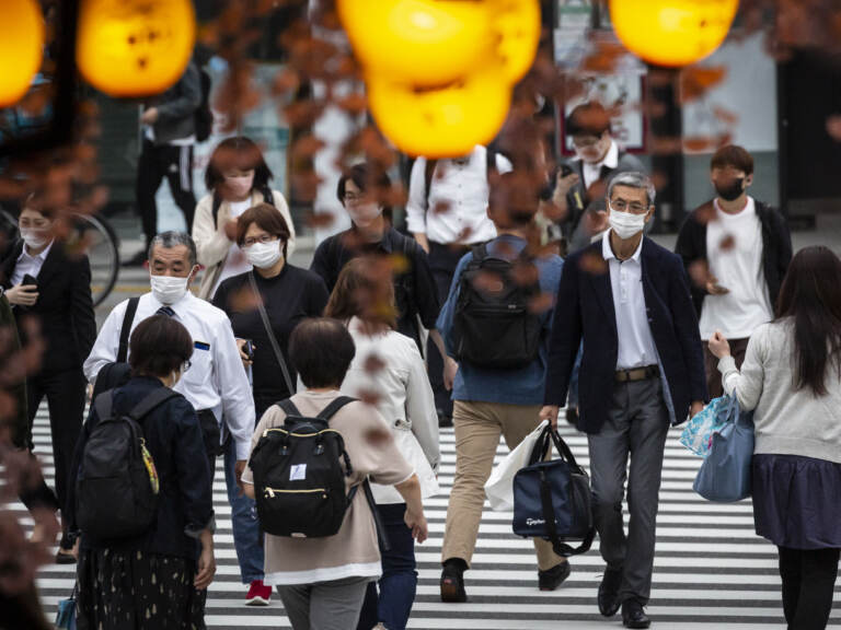 People in Tokyo wear masks on May 7. Daily coronavirus infections in Japan's capital have topped 4,000 — nearly four times as many as a week ago. (Yuichi Yamazaki/Getty Images)