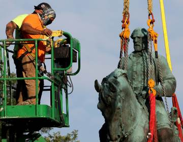 Workers remove a statue of Confederate Gen. Robert E. Lee from Market Street Park on Saturday in Charlottesville, Va. (Win McNamee/Getty Images)