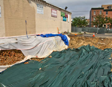 Residents are speculating that a torn up parking lot at 5th and Spring Garden Streets in Philadelphia is a grave sit in the midst of excavation. (Kimberly Paynter/WHYY)