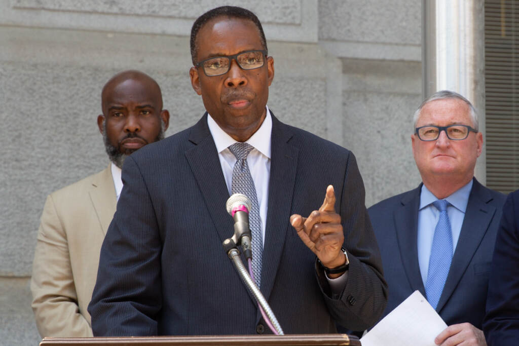 Darrell Clarke gestures while speaking from a podium, with other elected officials behind him