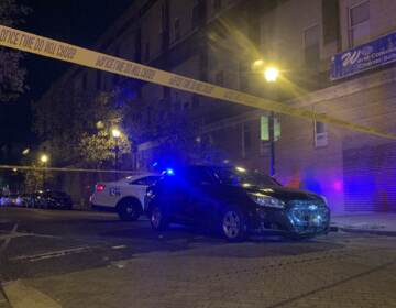 A car is pictured behind crime scene tape