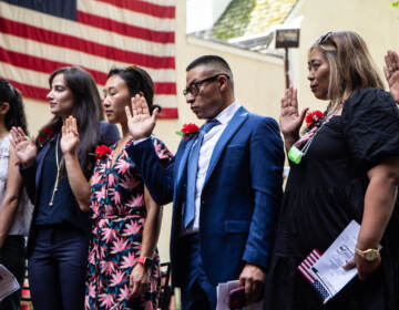 People participate in a naturalization ceremony at the Betsy Ross House