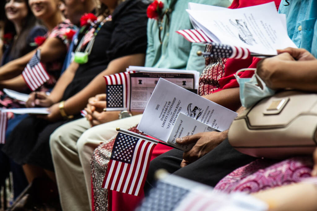 People hold American flags and papers during a naturalization ceremony