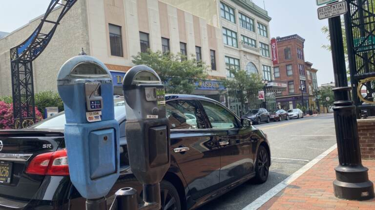 Parking meters are pictured in front of a car parked in Wilmington