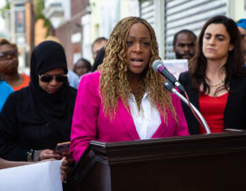 Philadelphia 3rd District Councilmember Jamie Gauthier speaks from a podium at a press conference, with elected officials behind her