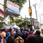 Philadelphia elected officials and community leaders gather outside a convenient store for a press conference, with a crowd in the foreground