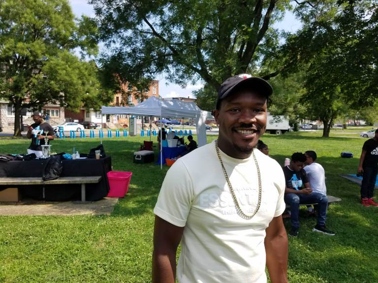 Raheem Manning stands outside at a block party