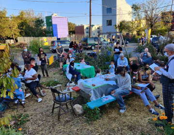Residents attend an outdoor event with picnic tables