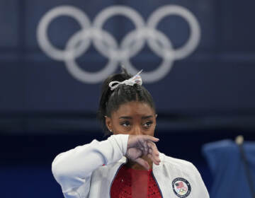 Simone Biles watches gymnasts perform after she exited the team