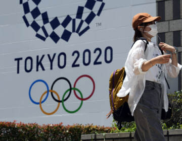 A woman wearing a protective mask walks with a baseball cap to shield from the sun walks in front of a Tokyo 2020 display