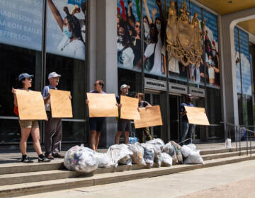Protesters hold signs in front of bags of trash on the steps of the MSB