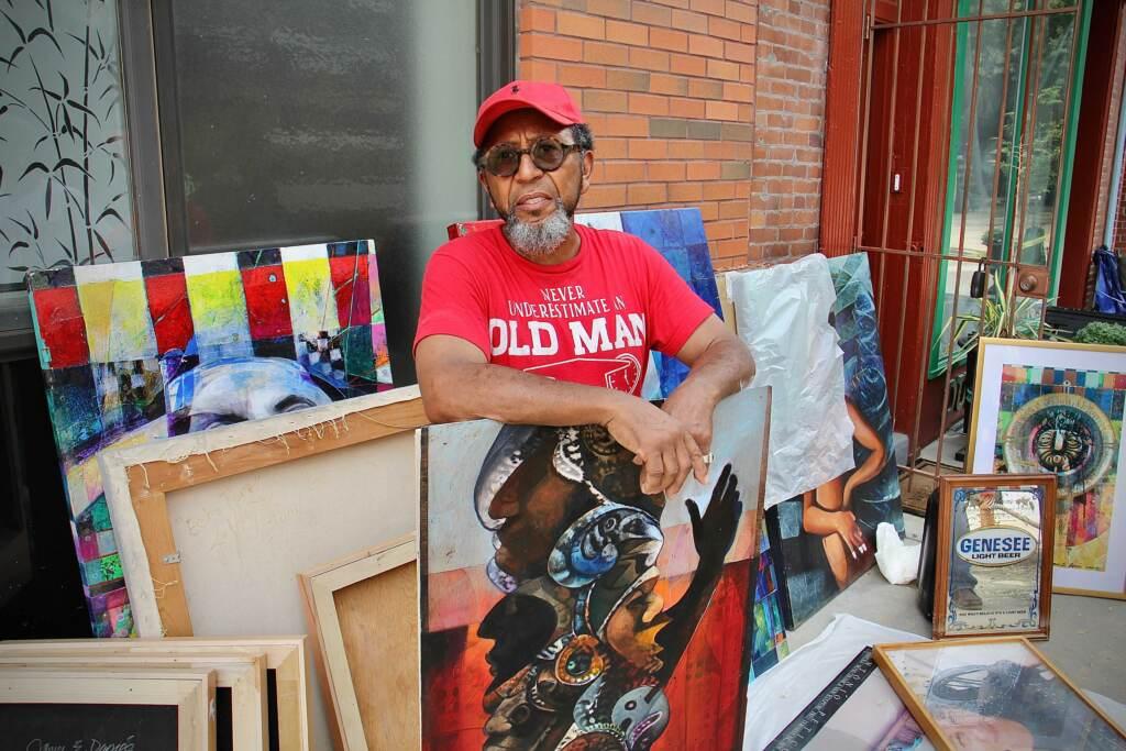 Philadelphia artist James Dupree stacks water-damaged paintings outside his galler