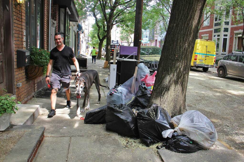 Water damaged possessions are piled at the curb on 6th Street as a resident and their dog walk by