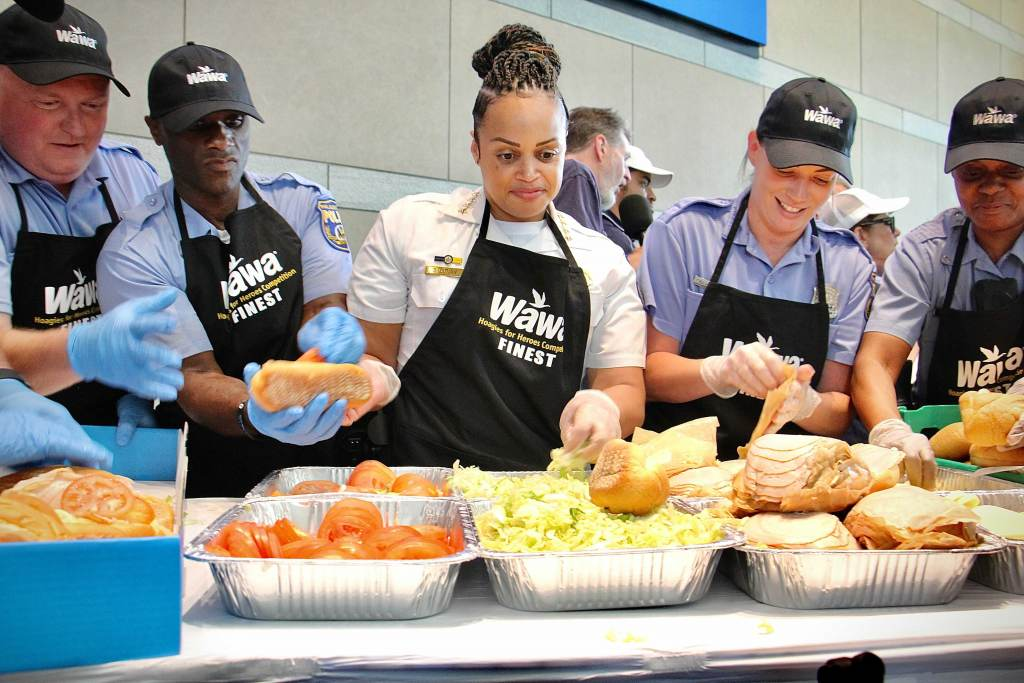 Philadelphia Police Commissioner Danielle Outlaw (center) and members of the police department compete against the fire department in a hoagie-making race