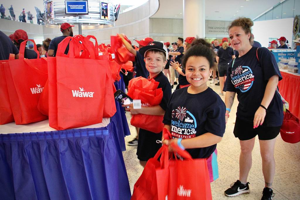 Alex Avallon and Sereniti Fripps help out with Wawa Hoagie Day at the National Constitution Center with their moms