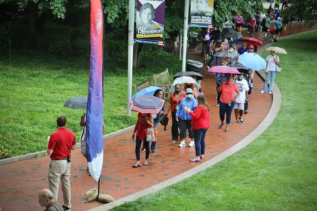 People stand in the rain outside the National Constitution Center