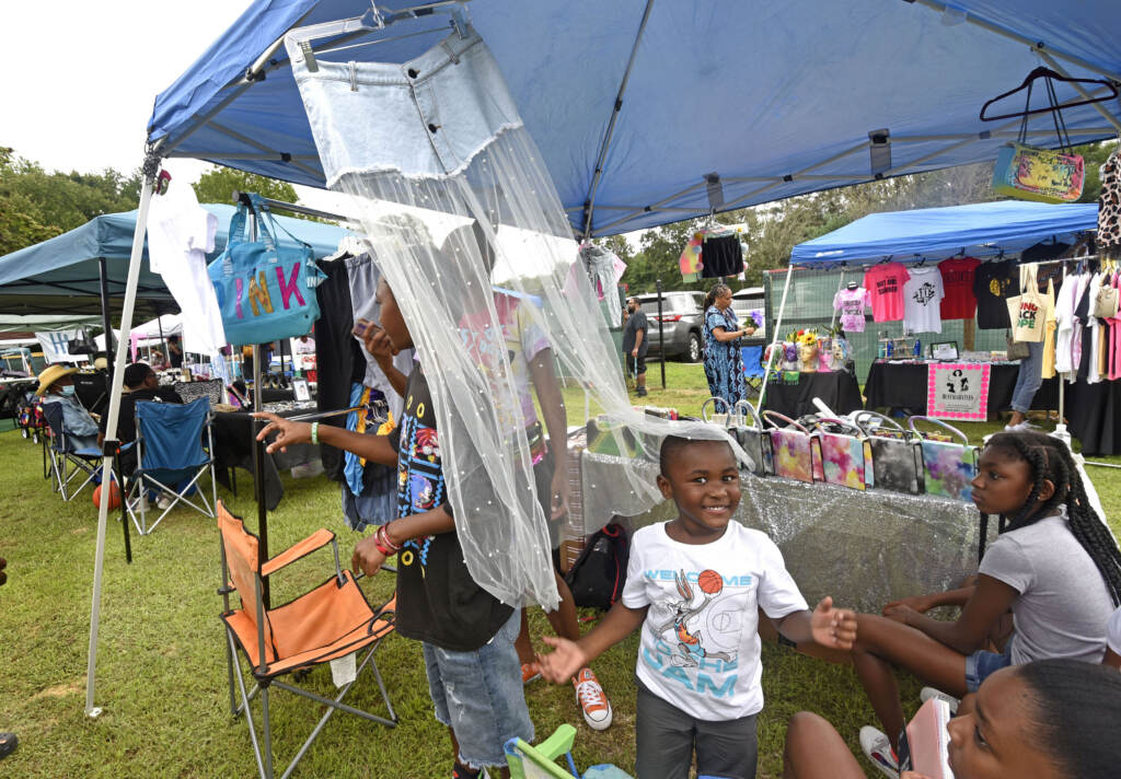 A family is pictured at a booth at the grand opening of the Mask Melanin Market in Glassboro NJ
