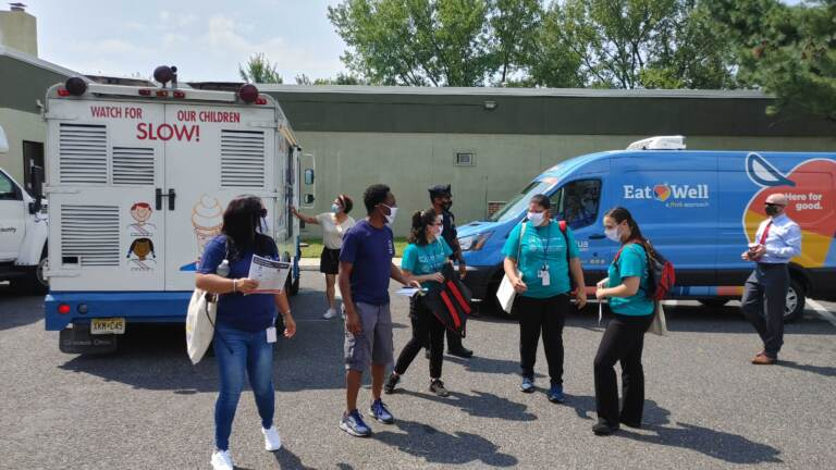 Vaccine team goes out to knock on doors as an ice cream truck waits to offer sweet treats in Camden (Tom MacDonald/WHYY)