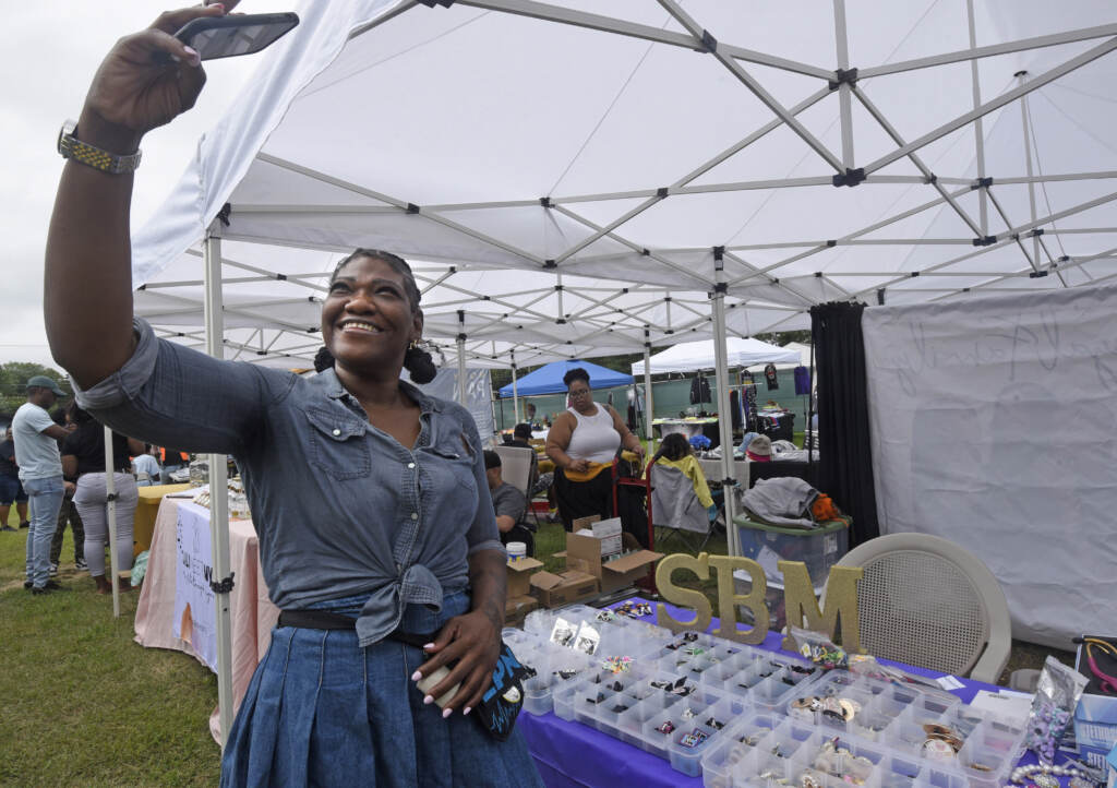 Vendor takes selfie at Mask Melanin Market.