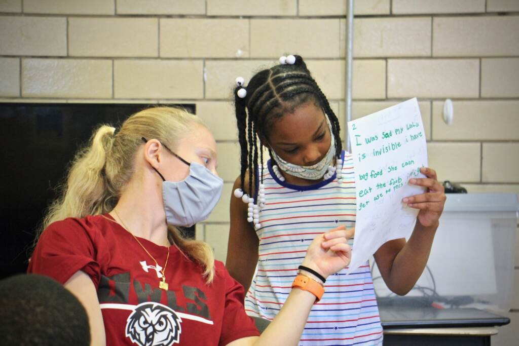 Instructor Emily Rankin helps 10-year-old Paris Counts with her writing