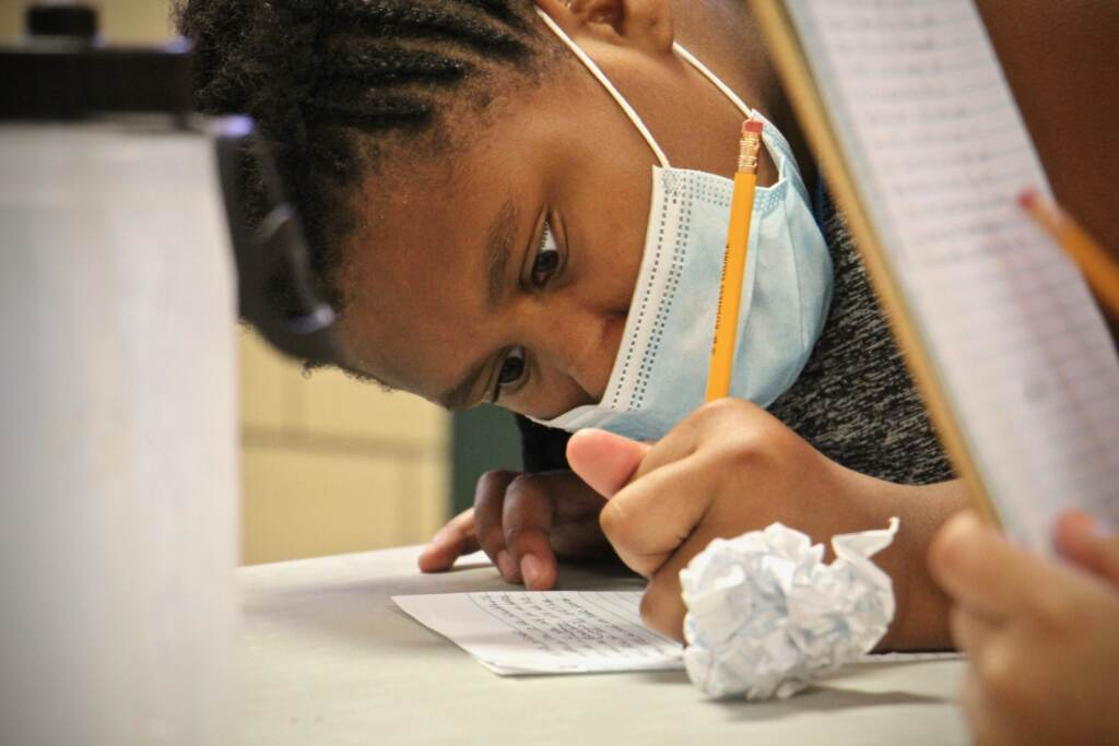 Jaydalee Rivera writes a story while wearing a face mask