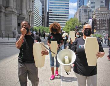 Activists carry small coffins as they march around City Hall