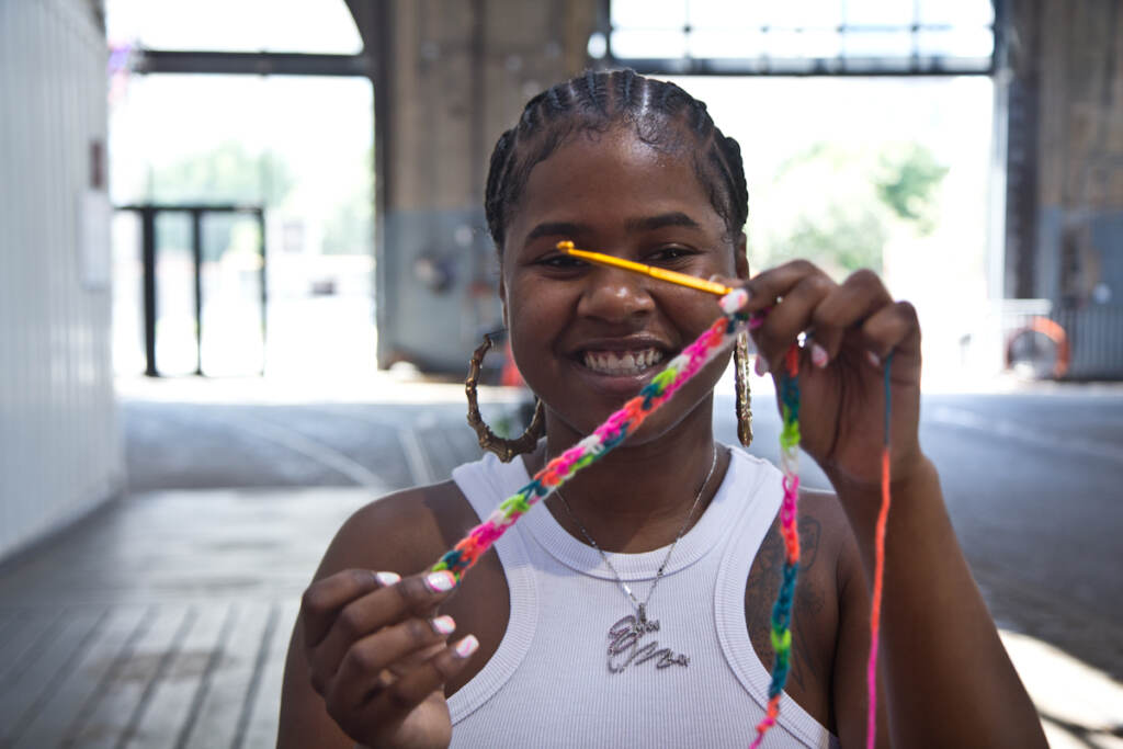 Emani Outterbridge holds up yarn