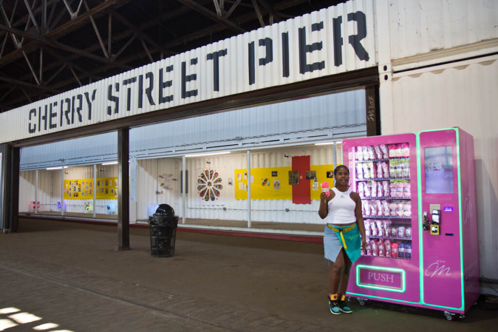 Emani Outterbridge holds up yarn in front of one of her vending machines, with Cherry Street Pier signage behind her