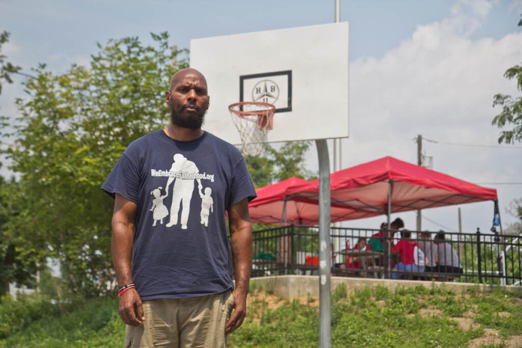 Derrick Pratt stands in front of a basketball hoop