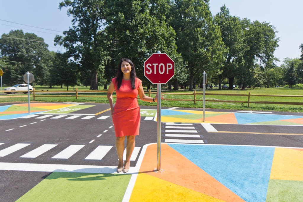 Stephanie Rivera Fenniri stands next to a stop sign at Lil' Philly Safety Village