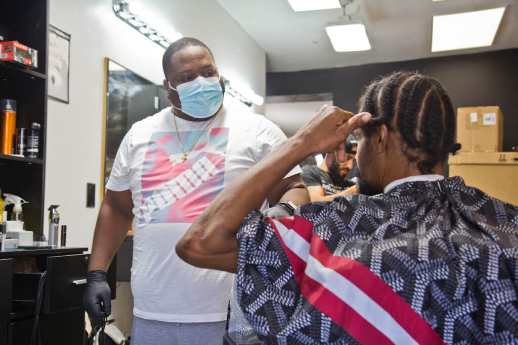 Javan Rankines gives someone a haircut while wearing a face mask