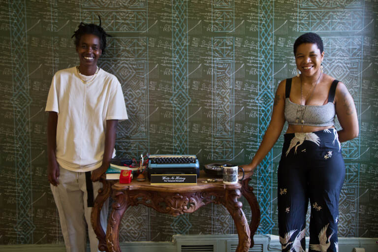 """Camae Ayewa (left) and Rasheedah Phillips (right), the artists of Black Quantum Futurism and makers of the film """"Write No History"""" with their work in Philadelphia's historic Hatfield House"""