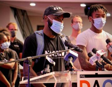 James Aye, wearing a mask, speaks at a DAO press conference