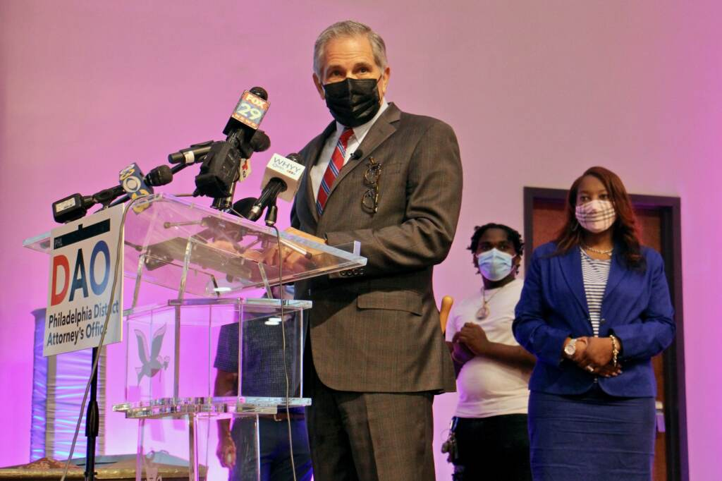 Larry Krasner, wearing a mask, speaks at a DAO press conference
