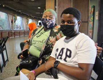 Viola Dales brought her son Raheem Dales, a sophomore at Parkway West High School, to the Philadelphia Zoo to get his COVID-19 vaccine. (Emma Lee/WHYY)