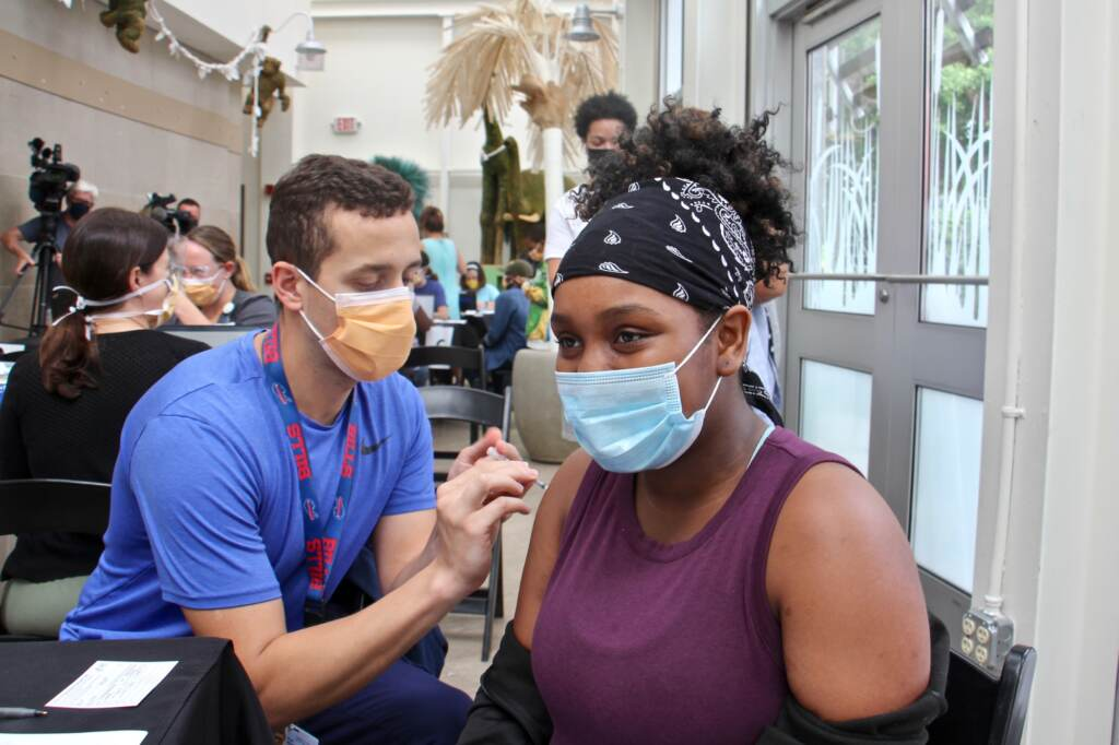 Zaliyah Dozier, an 11th grader at Lankenau high School gets her first shot of the COVID-19 vaccine during a clinic at the Philadelphia Zoo