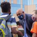 Superintendent William Hite greets students while wearing a face mask