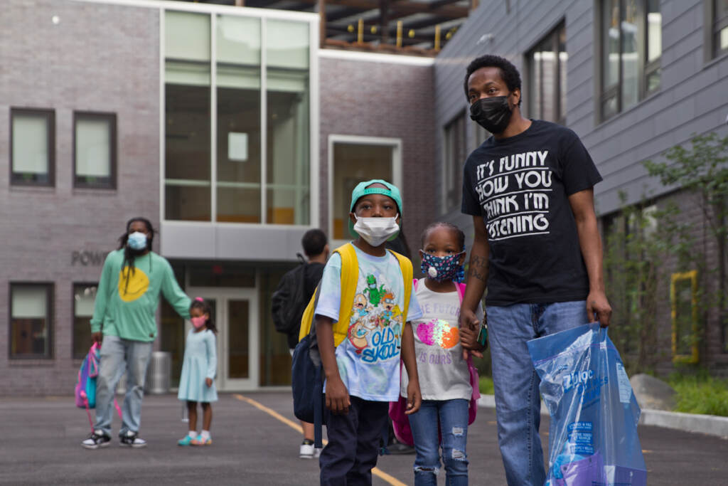 A family poses for a photo while wearing face masks outside their school