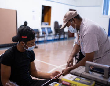 Saif Ashshaheed, 17, reviews reviews how to use a ruler with instructor Greg Palmer at the Dixon House community center in South Philadelphia on Tuesday, August 11, 2021. (Kriston Jae Bethel for WHYY)