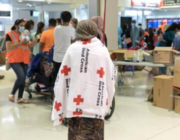An evacuee wears an American Red Cross blanket inside Philadelphia International Airport