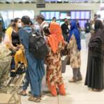 Evacuees stand inside Philadelphia International Airport