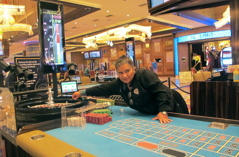This June 28, 2021 photo shows a dealer at the Hard Rock casino in Atlantic City NJ conducting a game of roulette. Figures released Aug. 10, 2021 by the American Gaming Association show the nation's commercial casinos had their best second quarter in history, with $13.6 billion in revenue, and are on pace to have their best year ever in 2021 as gamblers return to in-person casinos. (AP Photo/Wayne Parry)