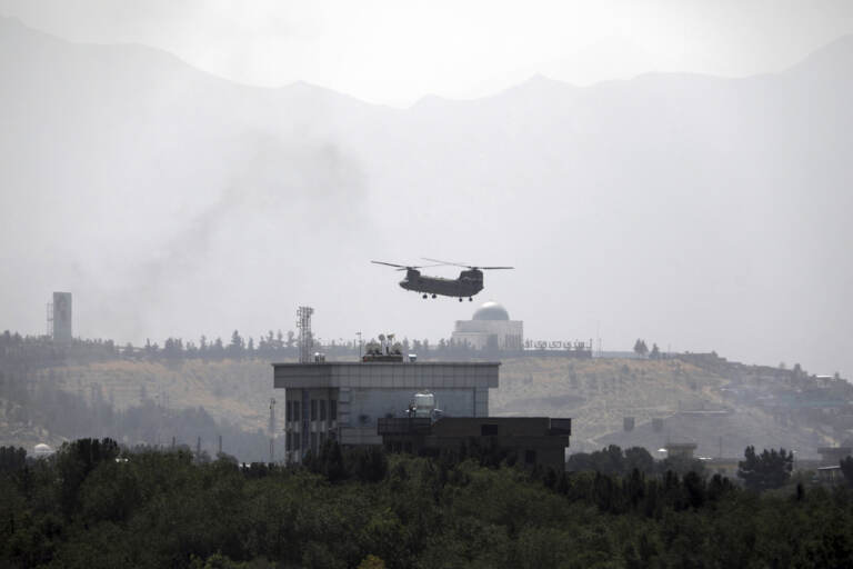 A U.S.Chinook helicopter flies over the U.S. Embassy, in Kabul, Afghanistan, Sunday, Aug. 15, 2021. Helicopters are landing at the U.S. Embassy in Kabul as diplomatic vehicles leave the compound amid the Taliban advanced on the Afghan capital. (AP Photo/Rahmat Gul)
