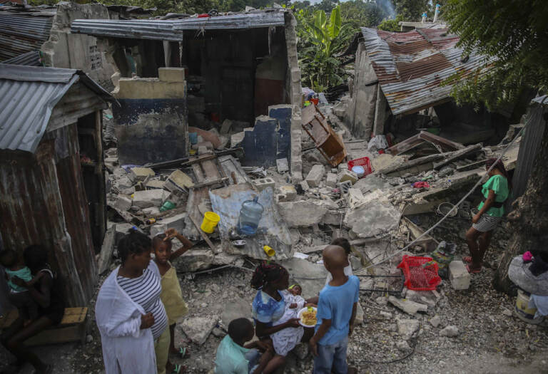 A family eats breakfast in front of homes destroyed by a 7.2 magnitude earthquake in Les Cayes, Haiti, Sunday, Aug. 15, 2021. (AP Photo/Joseph Odelyn)